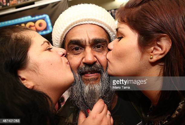 Osama bin Laden lookalike Ceara Francisco Helder Braga Fernandes poses with girls in his 'Bar do Bin Laden' on April 29 2014 in Sao Paulo Brazil...