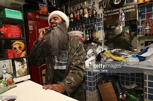 Osama bin Laden lookalike Ceara Francisco Helder Braga Fernandes laughs while chatting on the phone in his 'Bar do Bin Laden' on April 29 2014 in Sao...