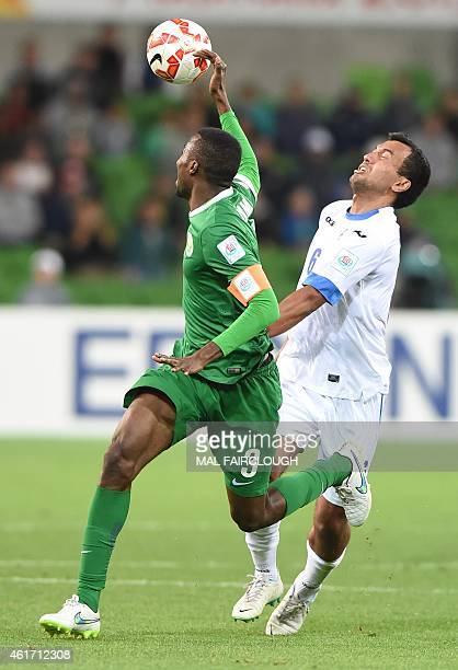 Osama Hawsawi of Saudi Arabia handballs the ball while under pressure from Bakhodir Nasimov of Uzbekistan during the Group B Asian Cup football match...