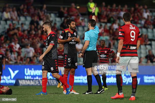 Osama Malik of Adelaide United gets a yellow card from referee Jarred Gillett in the round 26 clash against the Wanderers at Parramatta Stadium...
