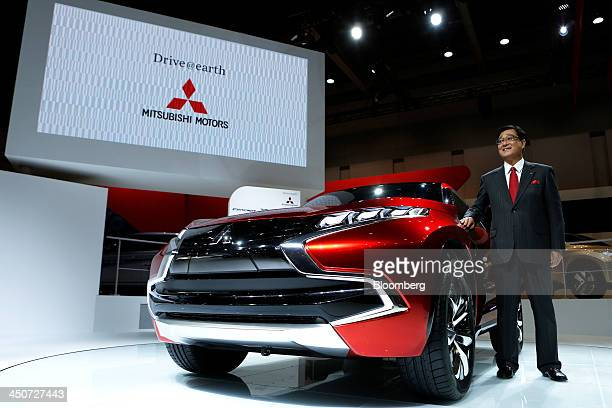 Osamu Masuko president of Mitsubishi Motors Corp poses for a photograph next to the company's Concept XRPHEV vehicle during a news conference at the...