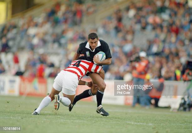 Osamu Ota tackles Eric Rush during the pool stage game between Japan and New Zealand at the 1995 Rugby World Cup the Free State Stadium Bloemfontein...