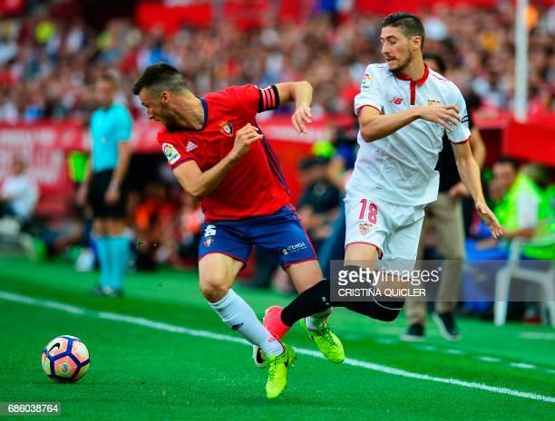 Osasuna's defender Oier Mate vies for the ball with Sevilla's defender Sergio Escudero during the Spanish league football match Sevilla FC vs CA...