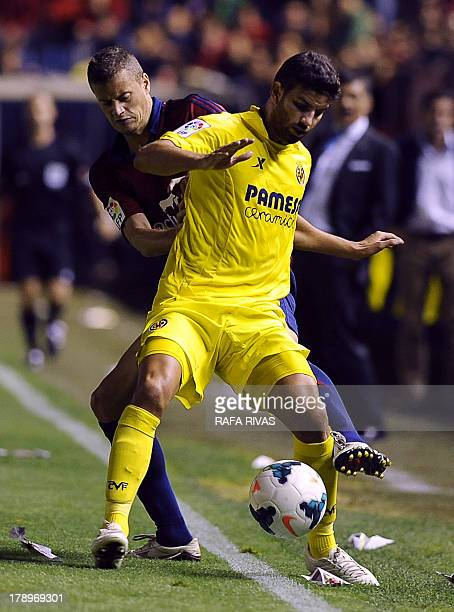 Osasuna's forward Oriol Riera vies with Villarreal's Argentinian defender Mateo Musacchio during the Spanish league football match Club Atletico...