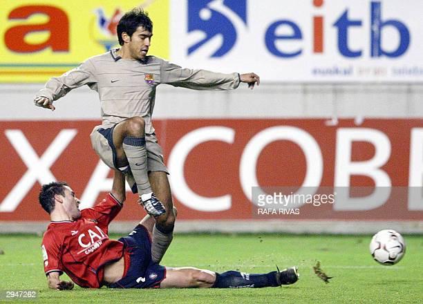Osasuna's Jose Izquierdo vies with Barcelona's Dutch Van Bronckhorst 08 February 2004 during a Spanish Liga soccer match at the Sadar stadium in...