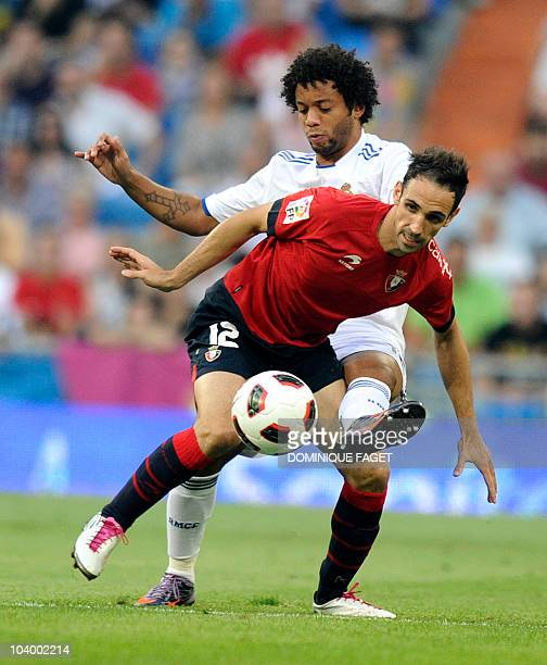 Osasuna's midfielder Juan Francisco Torres vies with Real Madrid's Brazilian defender Marcelo for the ball with during their Spanish league football...