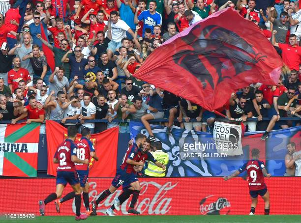 Osasuna's Spanish midfielder Roberto Torres celebrates with teammates after scoring during the Spanish league football match CA Osasuna against FC...