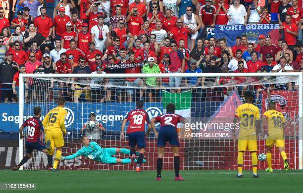Osasuna's Spanish midfielder Roberto Torres scores a penalty against Barcelona's German goalkeeper MarcAndre Ter Stegen during the Spanish league...