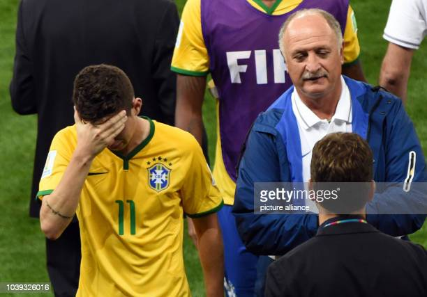 Oscar and head coach Luiz Felipe Scolari of Brazil react after the FIFA World Cup 2014 semi-final soccer match between Brazil and Germany at Estadio...