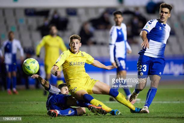 Oscar Arribas of AD Alcorcon is brought down by Jaime Sanchez and Iker Undabarrena of CE Sabadell FC resulting in a penalty kick awarded to AD...