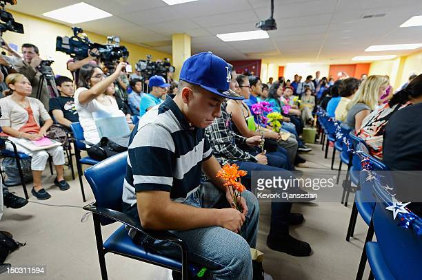 Oscar Barrera Gonzalez along with a group of immigrants known as DREAMers hold flowers as they listen to a news conference to kick off a new program...