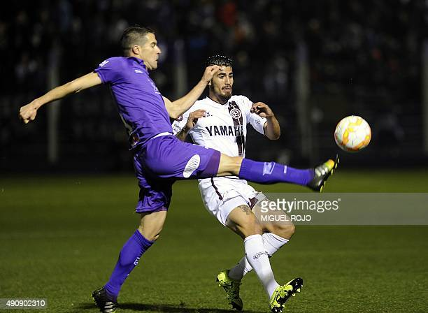 Oscar Benitez of Argentina's Lanus vies for the ball with Andres Scotti of Uruguay's Defensor Sporting during their Sudamericana Cup football match...