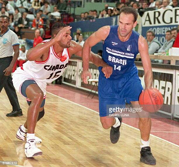 Oscar Bexerra Smith from the Brazilian basketball team tackles Wayne Yearunod from Canada 23 Aug at the Ruca Che stadium of Neuquen Argentina during...