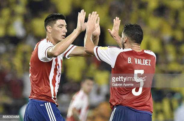 Oscar Cardozo of Paraguay celebrates with teammate Bruno Valdez after scoring the first goal of his team during a match between Colombia and Paraguay...