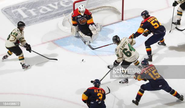 Oscar Dansk of the Erie Otters looks to stop a scoring chance by Matt Rupert and Ryan Rupert of the London Knights in an OHL game on October 19 2012...