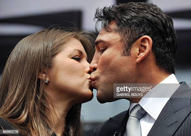 Oscar De La Hoya kisses his wife Millie Corretjer after announcing his retirement from boxing during a press conference in Los Angeles on Tuesday...
