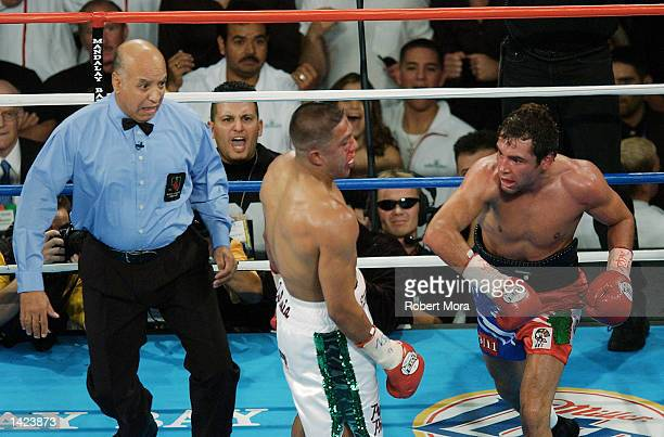 Oscar De La Hoya lands a right hook against Fernando Vargas as referee Joe Cortez looks on during their world super welterweight /Jr middleweight...