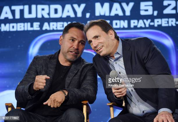 Oscar De La Hoya promoter of Canelo Alvarez speaks with Tom Loeffler promoter of Gennady Golovkin during a news conference at Microsoft Theater at LA...