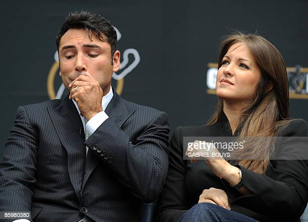 Oscar De La Hoya reacts beside his wife Millie Corretjer after announcing his retirement from boxing during a press conference in Los Angeles on...