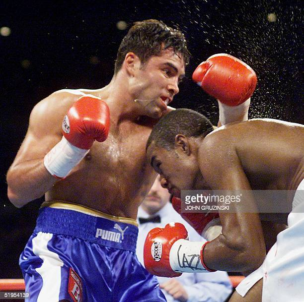Oscar de la Hoya , the WBC Welterweight champion from the US, lands a glancing right off the back of Felix Trinidad, the IBF Welterweight champion...