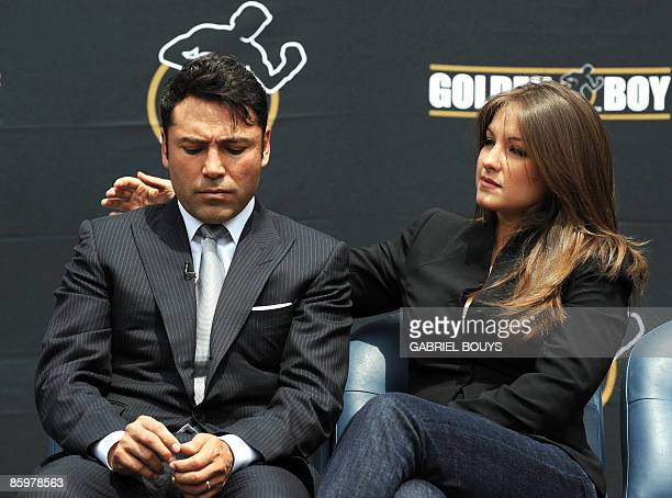 Oscar De La Hoya's wife Millie Corretjer consoles him after he announced his retirement from boxing during a press conference in Los Angeles on April...