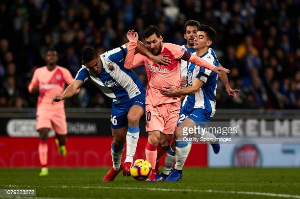 Oscar Duarte and Marc Roca of RCD Espanyol tries to stop Lionel Messi of FC Barcelona during the La Liga match between RCD Espanyol and FC Barcelona...
