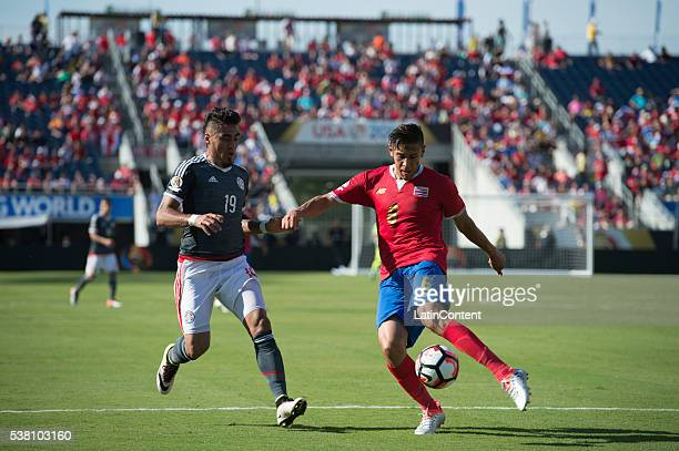 Oscar Duarte of Costa Rica clears the ball from Dario Lezcano during the group A match between Costa Rica and Paraguay at Camping World Stadium as...