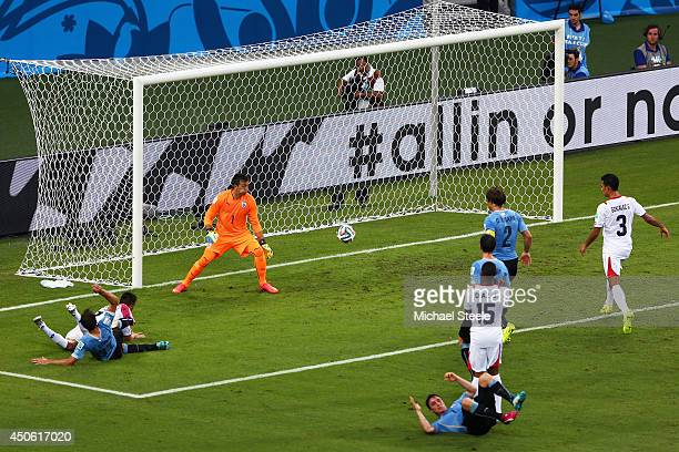 Oscar Duarte of Costa Rica puts the ball past Fernando Muslera of Uruguay on a diving header for his team's second goal during the 2014 FIFA World...