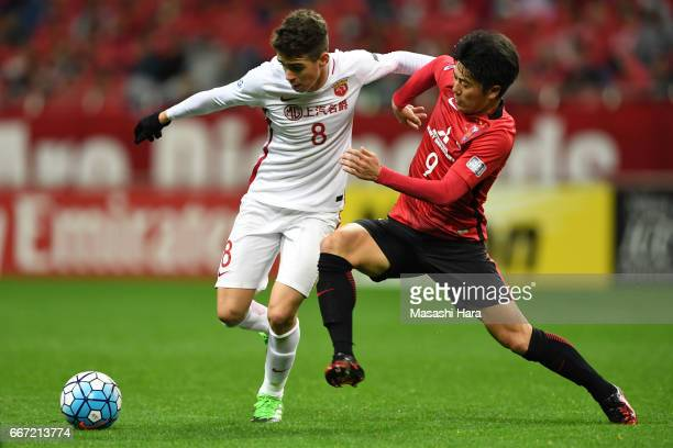 Oscar Emboaba Junior of Shanghai SIPG and Yuki Muto of Urawa Red Diamonds compete for the ball during the AFC Champions League Group F match between...