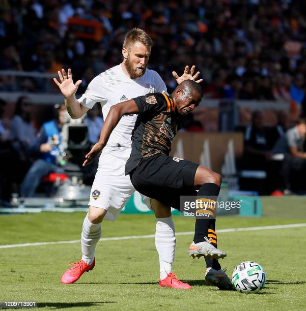 Oscar Garcia of Houston Dynamo feels the pressure from Aleksander Katai of Los Angeles Galaxy as he attempts to bring the ball up the field during...