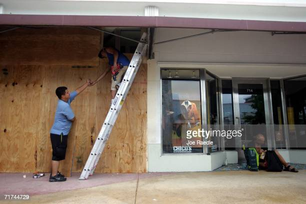 Oscar Gomez and Luis Loaiza place plywood over the windows of a business on a deserted South Beach's Lincoln Road as they prepare for the approaching...