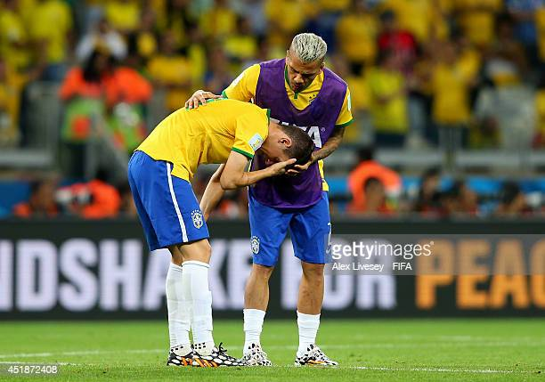 Oscar is consoled by his teammate Dani Alves of Brazil after 17 defeat in the 2014 FIFA World Cup Brazil Semi Final match between Brazil and Germany...
