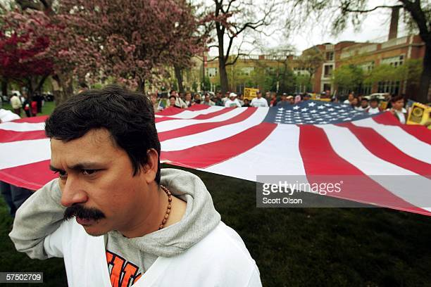 Oscar Jimenez helps to carry a giant American flag to an immigrant rights march starting at noon May 1 2006 in Chicago Illinois Organizers of the...