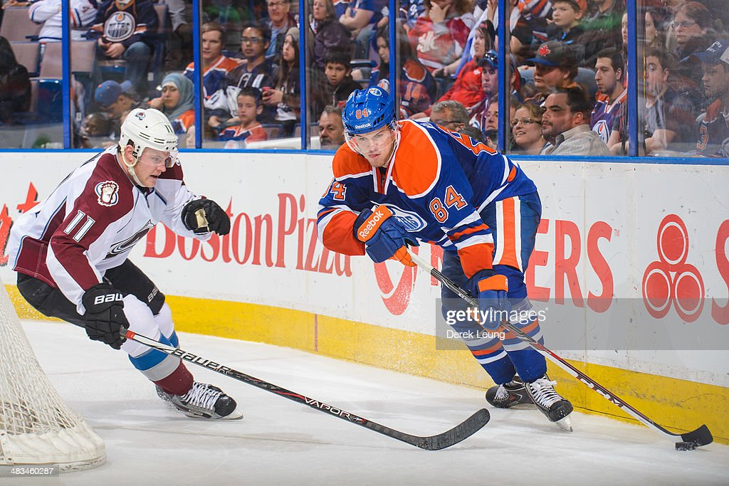 Oscar Klefbom #84 of the Edmonton Oilers battles for the puck against Jamie McGinn #11 of the Colorado Avalanche during an NHL game at Rexall Place on April 8, 2014 in Edmonton, Alberta, Canada. The Avalanche defeated the Oilers 4-1.