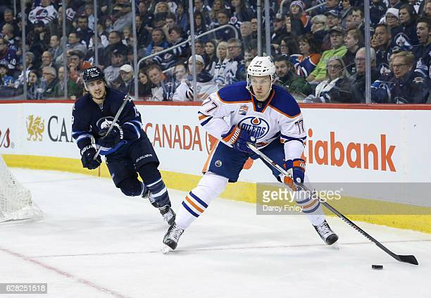 Oscar Klefbom of the Edmonton Oilers plays the puck along the boards as Brandon Tanev of the Winnipeg Jets gives chase during first period action at...