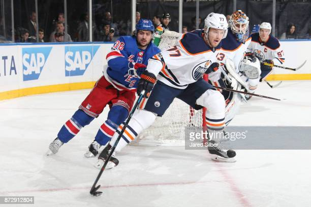 Oscar Klefbom of the Edmonton Oilers skates with the puck against Mats Zuccarello of the New York Rangers at Madison Square Garden on November 11...