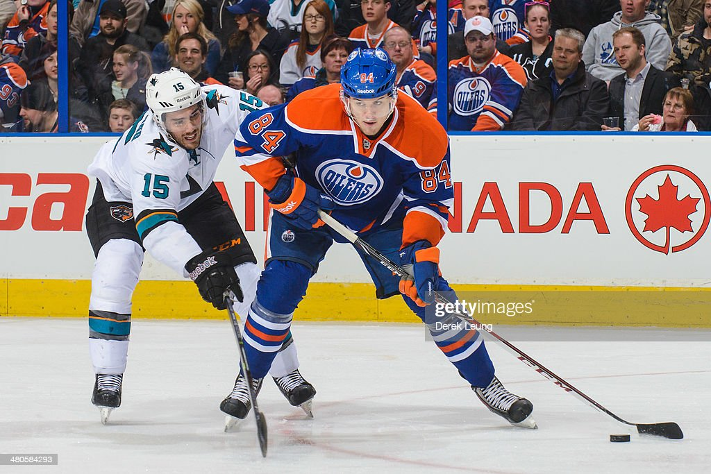 Oscar Klefbom #84 of the Edmonton Oilers skates with the puck as James Sheppard #15 of the San Jose Sharks tries to check him during an NHL game at Rexall Place on March 25, 2014 in Edmonton, Alberta, Canada. The Sharks defeated the Oilers 5-2.