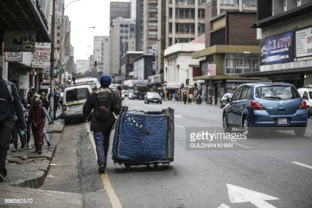 Oscar Maile pulls his trolley as he collects waste in Johannesburg city on June 27 2018 Oscar Maile has been doing this for three years and says...