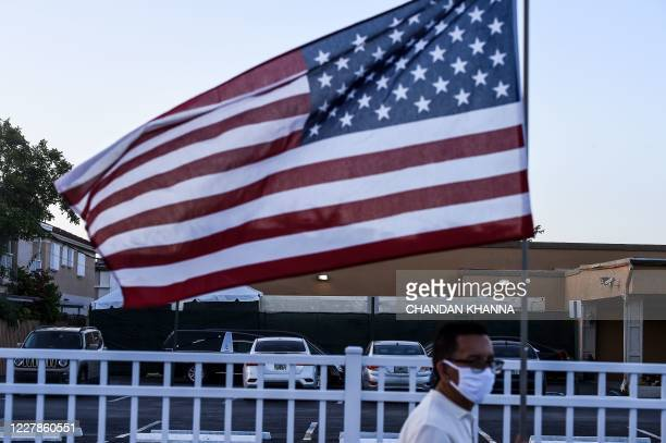 Oscar Marquez a member of Association of the El Portal condominium walks with a US flag as the container of corpses is seen in the background hidden...