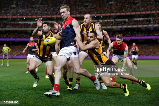 Oscar McDonald of the Demons is tackled by LR Paul Puopolo Jarryd Roughead and Jarman Impey of the Hawks during the 2018 AFL First Semi Final match...