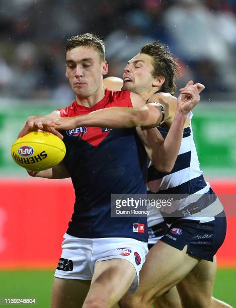 Oscar McDonald of the Demons kicks whilst being tackled by Tom Atkins of the Cats during the round two AFL match between the Geelong Cats and the...