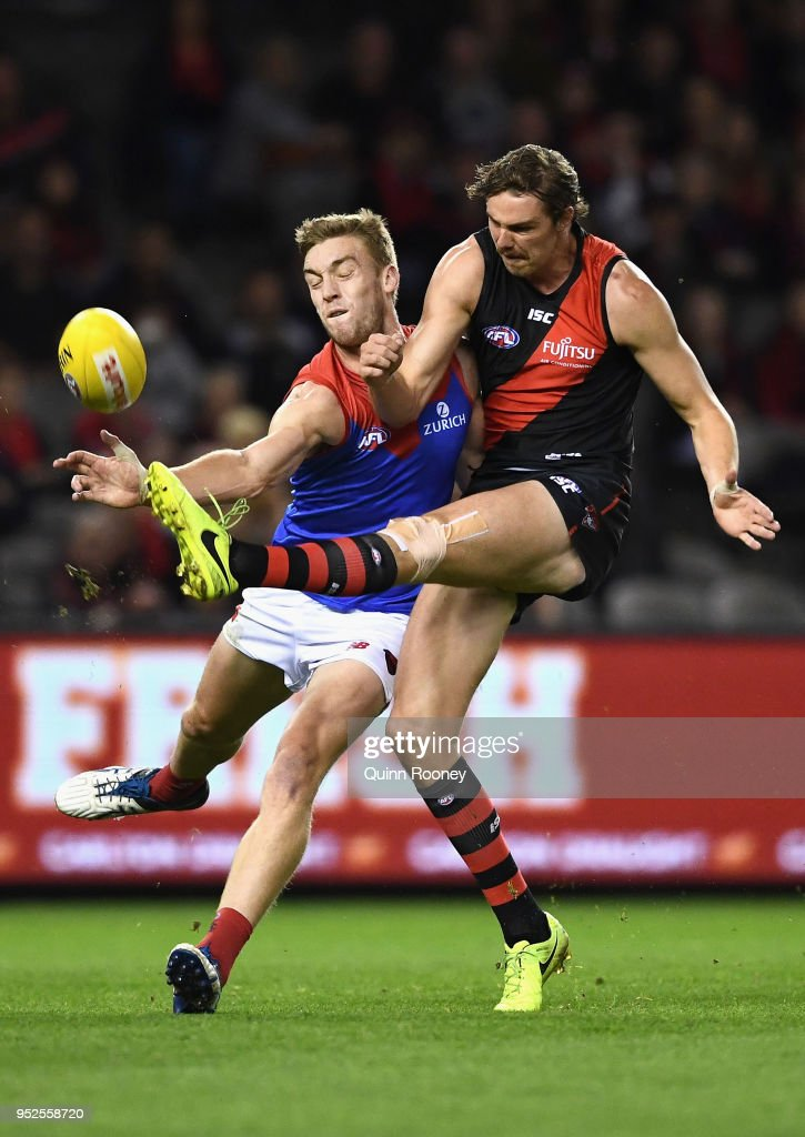 Oscar McDonald of the Demons smouthers a kick by Joe Daniher of the Bombers during the round 6 AFL match between the Essendon Bombers and Melbourne Demons at Etihad Stadium on April 29, 2018 in Melbourne, Australia.