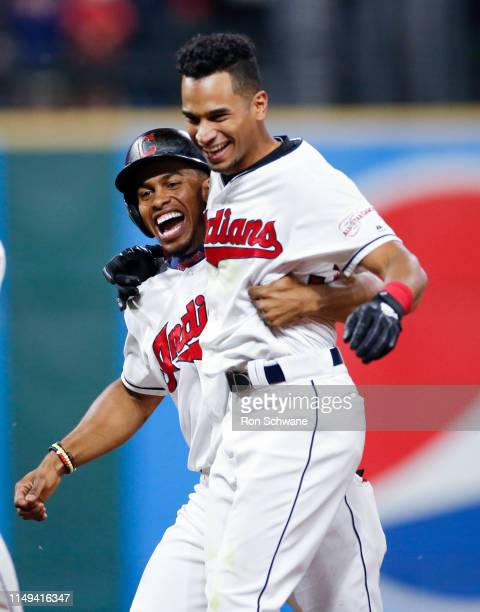 Oscar Mercado of the Cleveland Indians celebrates with Francisco Lindor after hitting the game winning single off Raisel Iglesias of the Cincinnati...