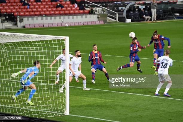 Oscar Mingueza of FC Barcelona scores their side's third goal past Alvaro Fernandez of SD Huesca during the La Liga Santander match between FC...