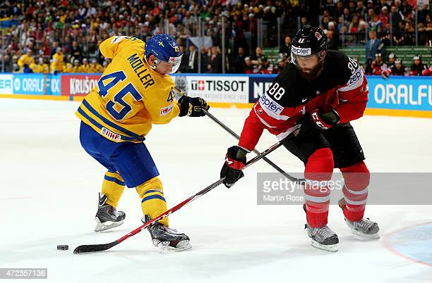Oscar Moller of Sweden and Brent Burns of Canada battle for the puck during the IIHF World Championship group A match between Sweden and Canada at o2...