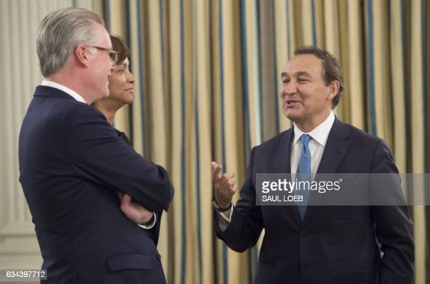 Oscar Munoz President and CEO of United Airlines speaks with Delta Air Lines CEO Ed Bastian as they attend a meeting with airline industry executives...