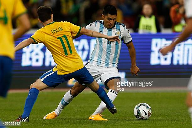 Oscar of Brazil and Enzo Perez of Argentina battle for the ball during a match between Argentina and Brazil as part of 2014 Super Clasico at Beijing...