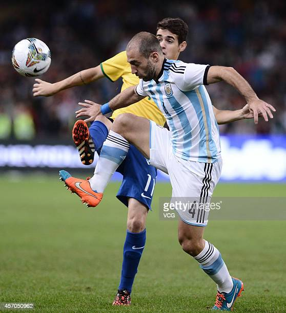 Oscar of Brazil and Pablo Zabaleta of Argentina battle for the ball during a match between Argentina and Brazil as part of 2014 Super Clasico at...