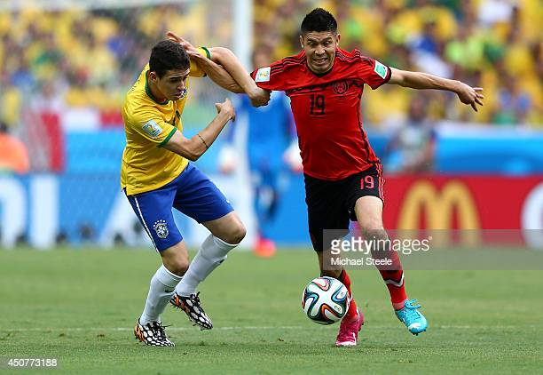 Oscar of Brazil challenges Oribe Peralta of Mexico during the 2014 FIFA World Cup Brazil Group A match between Brazil and Mexico at Castelao on June...