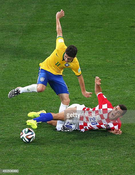 Oscar of Brazil is challenged by Mateo Kovacic of Croatia during the 2014 FIFA World Cup Brazil Group A match between Brazil and Croatia at Arena de...